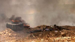 Palestinier tar skydd under sammandrabbningarna med israeliska soldater vid gränsstängslet.
