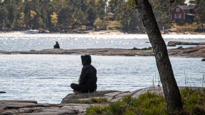 En människa sitter vid stranden och ser ut över vattnet.