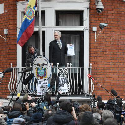 Wikileaks grundare Julian Assange visar upp FN-panelens utlåtande i ett tal inför medier och anhängare på Ecuadros ambassad i London i fredags