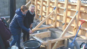Två kvinnor håller i en murslev tillsammans. De står på en byggarbetsplats och ska mura en grundsten.