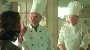 Stickan och Calle i köket. Stickan hötter med fingret åt en tredje person.