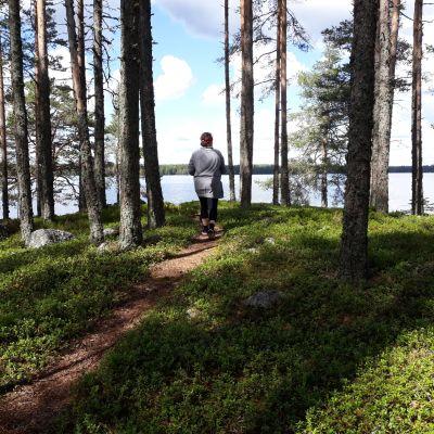 Nainen kävelee polkua pitkin saaressa aurinkoisena kesäpäivänä..