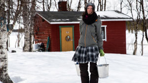 Katja Jomppanen ämpärit kädessä Turvejärven luontaistilan pihassa.