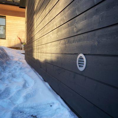 tuuletusaukko omakotitalon seinän alaosassa talvella