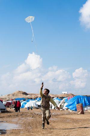 Pojke leker i ett läger i Ain Issa i Syrien