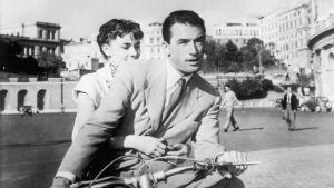 Audrey Hepburn ja Gregory Peck ajavat skootterilla Roomassa. Kuva elokuvasta Loma Roomassa.