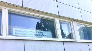 Ett fönster där man ser en skylt med texten: Raseborgs kulturinstitut, Raaseporin kulttuuriopisto. Vita marmorväggar.