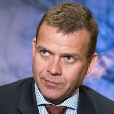 Petteri Orpo i mörk kostym. I bakgrunden en suddig tavla.