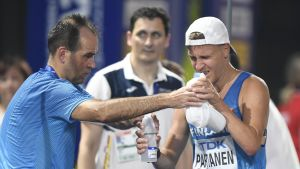 Veli-Matti Partanen får hjälp (bland annat vatten) av sin tränare.