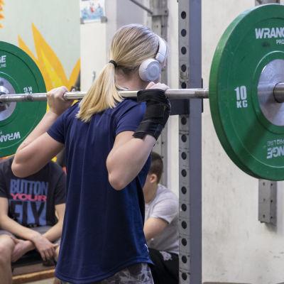 Ung kvinna lyfter tyngder i ett gym.