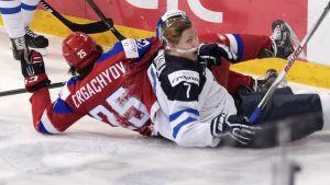 Två spelare ligger på isen i JVM-finalen