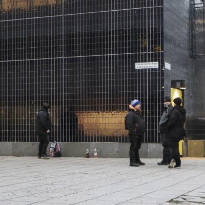 Tre män och en kvinna står utomhus i en betongmiljö. Bredvid en vägg står några lemonadflaskor.