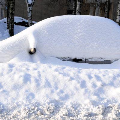En bil är täckt av snö.