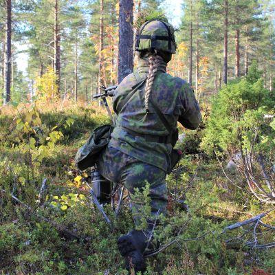 Anita Korva gör sin militärtjänstgöring i Kajanalands brigad. På bilden ses hon bakifrån stå i skogen i full krigsmundering.