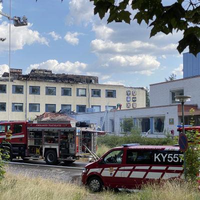 paloautoja palopaikalla, taustalla nosturista suihkutetaan vettä talon kytevälle ullakolle