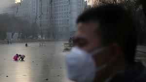 En man iklädd mask vid en frusen flod i Peking 16.12.2016