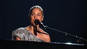 Alicia Keys sitter vid ett piano och sjunger i en mikrofon.