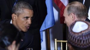 USA:s president Barack Obama och Rysslands president Vladimir Putin tittar på varandra.