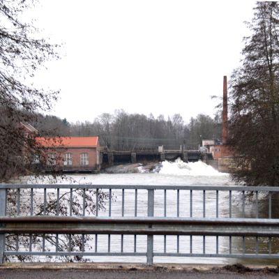 En bild tagen från en bro som föreställer en konstgjord fors där det forsar vatten. Runtom finns tegelhus.