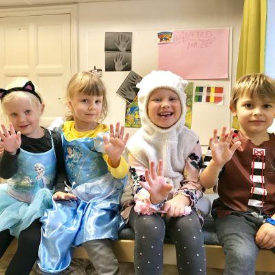 Fyra glada dagisbarn i maskeradkläder.