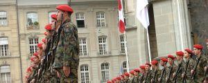Soldater står på ett torg. De har röda baretter på huvudet, och har stormgevär i handen. I bakgrunden syns Schweiz flagga.