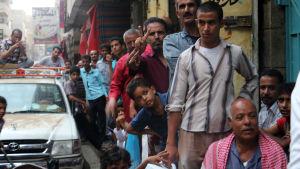 Jemeniter köar för att köpa mat och vatten i Taiz, Jemen, den 19 juni.