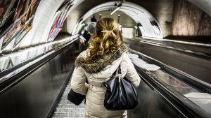 Kvinna i rulltrappa på metrostation