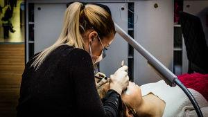 Kvinna hos kosmetologen