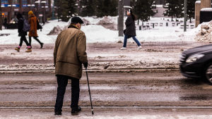 Äldre man går över gata