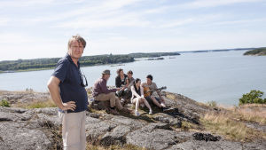 Miak Kaurismäki står på en klippa med skådespelarteamet bakom sig.