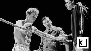 Kuva elokuvasta Hymyilevä mies: nyrkkeilijä nojaa käsillään kehän köysiin.