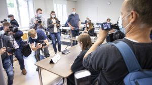 Den åtalade i skolattacksfallet i Kuopio sitter med ryggen mot kameran i en rättssal. Flera fotografer står framför honom och fotograferar. En fotograf syns på bild som står bakom mannen. Samtliga personer har munskydd på sig.