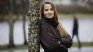 Kvinna lutar sig mot ett träd med armarna i kors och ler.