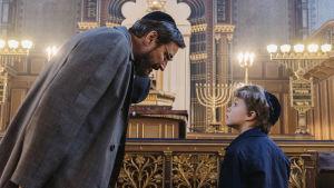 Morfar Josef (Peter Schildt) och Erik som barn (Walter Karlström) i en upplyst synagoga.