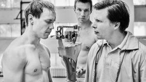 Boxaren Olli Mäki står på vågen inför kollega och tränare.