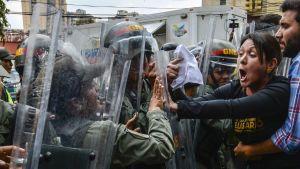 Den oppositionella kongressledamoten Amelia Belisario drabbar samman med kravallpolis utanför högsta domstolen i Caracas 30.3.2017