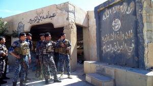 Irakisk polis framför en flagga som tillhör Islamiska staten.