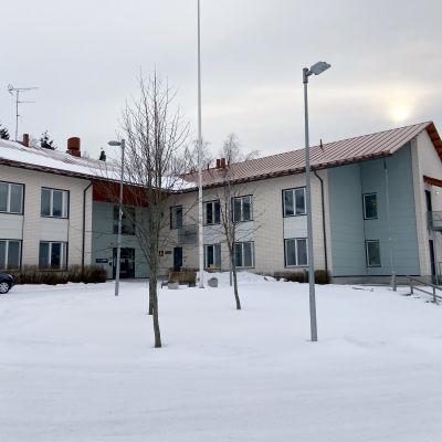 En byggnad i två våningar som fungerar som ett äldreboende. På marken ligger snö.