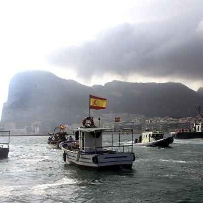 Spanska fiskebåtar med flaggor seglar förbi Gibraltarklippan.