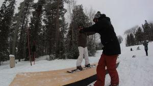 Pojke gör snowboardtricks på en dancefloor ramp