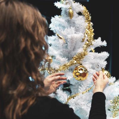 Nainen koristelee joulupuuta.