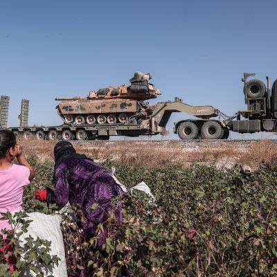 Nainen ja tyttö katsovat Turkin armeijan kuljettamaa tankkia Sanliurfassa Turkissa lähellä Syyrian rajaa.