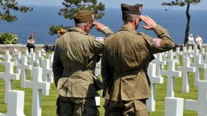 Amerikanska soldater står på en gravgård för offren på Normandie.