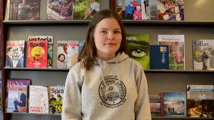 Sonja Kukkonen står framför en tidningsvägg i Borgå gymnasium