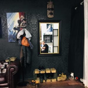 tatuointiartisti Kirill Shestakov tekee tatuointia asiakkaalla, Kirill näkyy liiketilan seinällä olevasta peilistä.