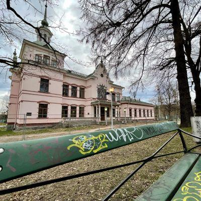 Vanha vaaleanpunainen rakennus puiston keskellä. Ympärillä metalliset työmaa-aidat. Etualalla vihreä puistonpenkki.