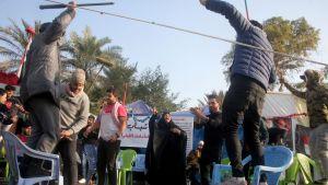 Män och kvinnor står på stolar och på marken och firar.