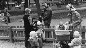 Perheitä ulkoilemassa leikkipuistossa.