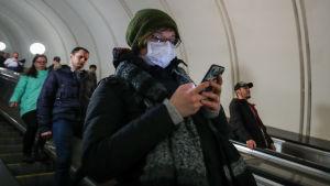 En kvinna med ansiktsskydd står i rulltrappor och knäpper på sin telefon.