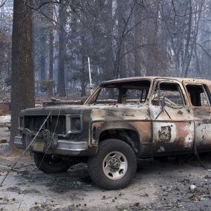 I förgrunden en bil som förstörts i skogsbrand, i bakgrunden ruinerna efter en byggnad.